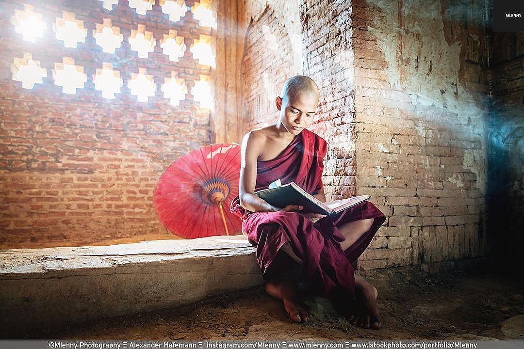 Silence. Burmese novice monk reading buddhist book in temple