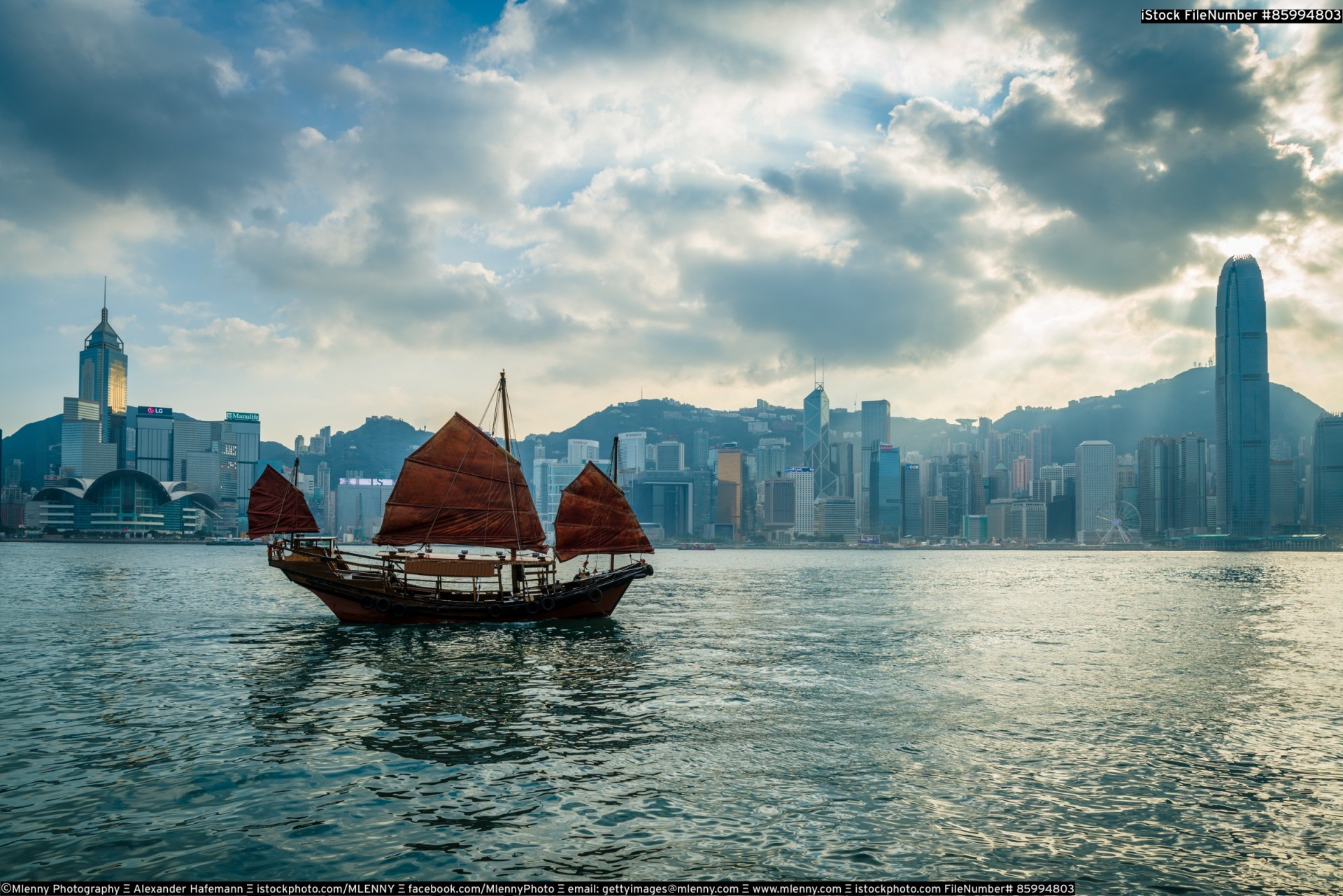 Junkboat sailing along skyline of Hong Kong